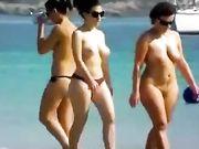 Dos mujeres en topless y desnudos en la playa